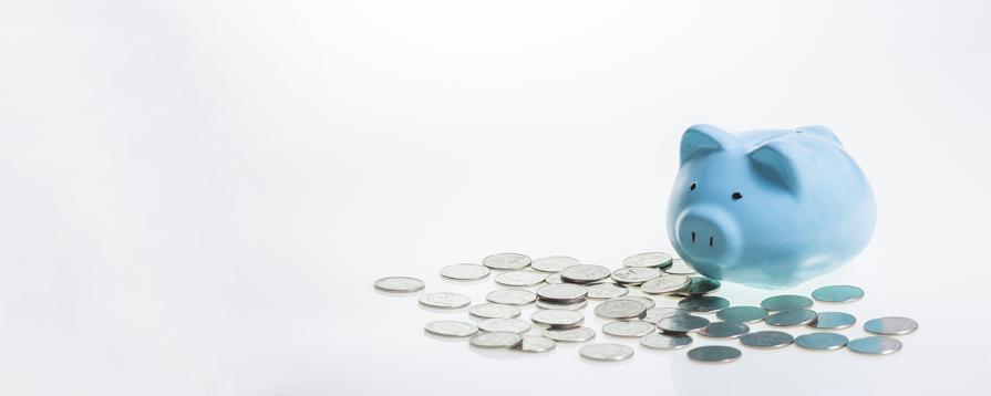 niebieska świnka-skarbonka stojąca na stercie pieniędzy